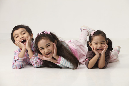 Happy Siblings Lying on Front, laughing