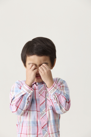 Portrait of young boy in checkered shirt on white backdrop, crying