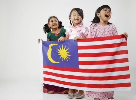 Three girls holding flag