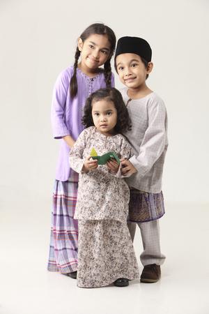 niños sosteniendo paquete verde Foto de archivo