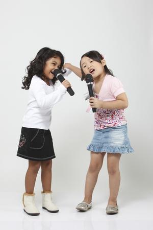 Due ragazze che cantano nei microfoni