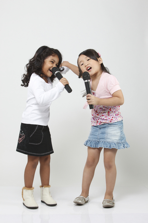 Two girls singing into microphones