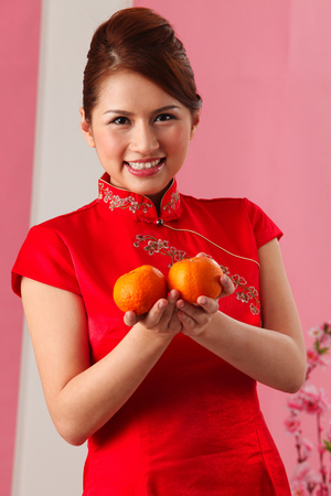 Young woman greeting and holding mandarin oranges