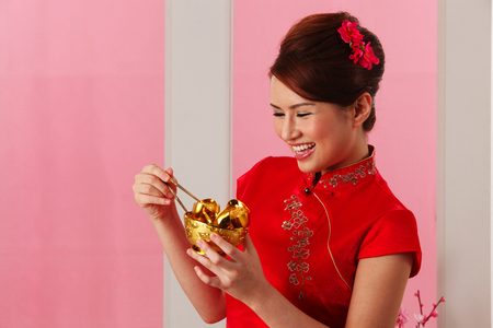 Young woman holding golden bowl