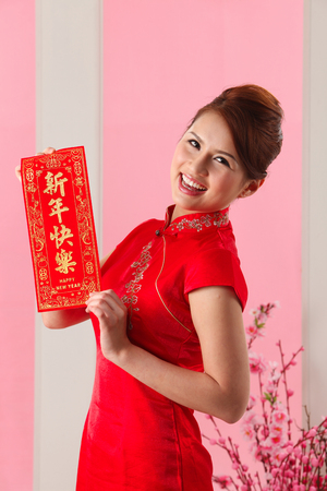 Young woman holding a red banner greeting Banco de Imagens