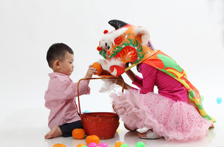 sisiter wearing lion dance custome playing with younger brother Banco de Imagens