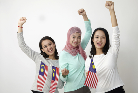 three multi racial malaysian holding flag wtih raised arm Standard-Bild