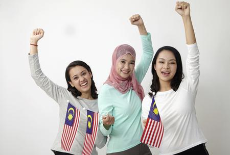 tres multirraciales malaysian sosteniendo la bandera con el brazo levantado