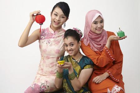 three malaysian woman holding lantern and oil lamp