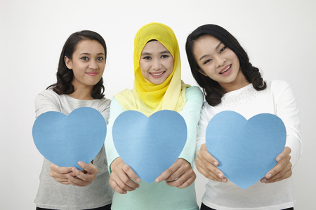 three multi racial malaysian holding heart shape cardboard looking at camera