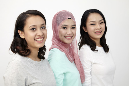three multi racial malaysiansstanding in a row  looking at camera Фото со стока