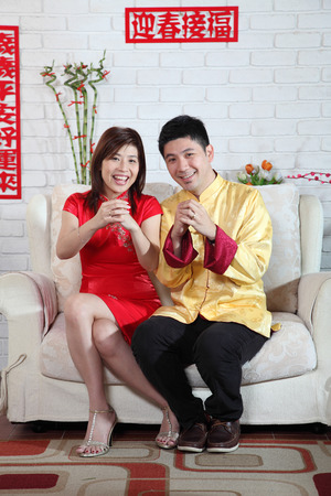 chinese couple sitting on the sofa with chinese new year decoration greeting