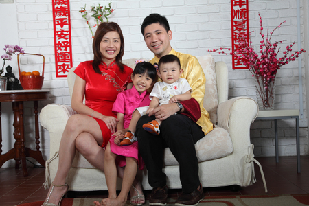 chinese family sitting on the sofa with chinese new year decoration Stock Photo