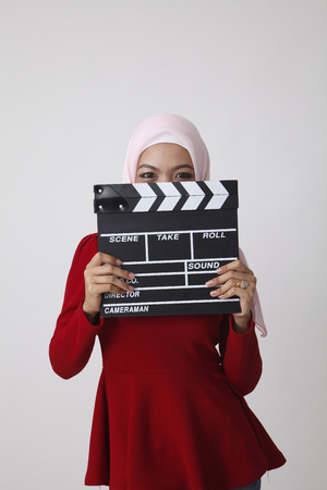 happy malay with red tudung hiding behind clapper board