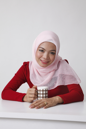 malay woman taking rest having a cup of tea Imagens