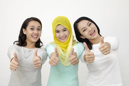 three Malaysian woman raising thumb Stock Photo