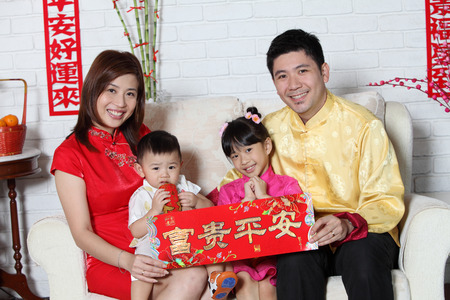 chinese family sitting on the sofa with chinese new year decoration Standard-Bild