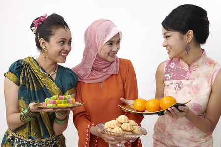 malaysian holding plate fill up with candy,bahulu and mandarin oranges