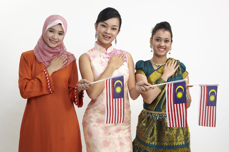 young women holding malaysia flag hand on the chest 스톡 콘텐츠