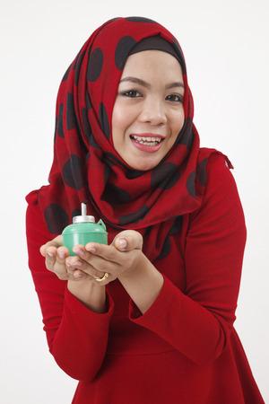 malay woman with tudung holding a pelita looking at camera
