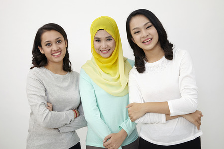 three multi racial malaysian standing side by side looking at camera