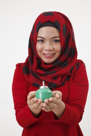 malay woman with tudung holding a pelita and focus on pelita Stock Photo