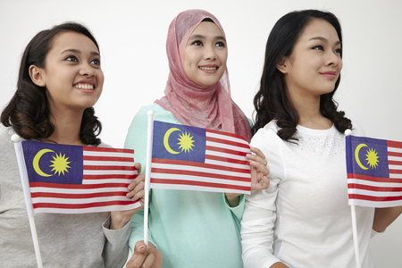Close up three multi racial malaysian holding flag looking away