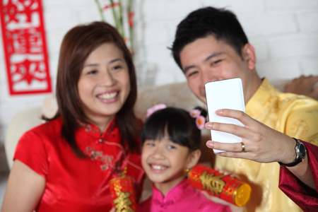 chinese family sitting on the sofa with chinese new year decoration Reklamní fotografie