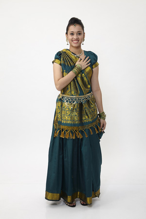 Indian woman wearing saree with hand on chest