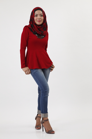 full length of malay woman with red tudung posing