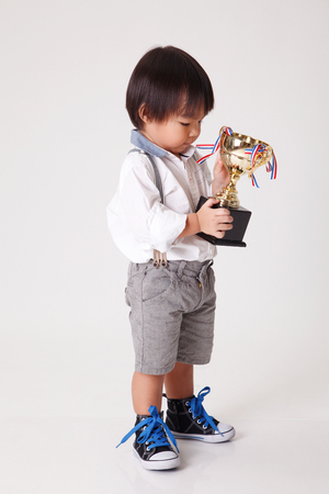 chinese boy with gold trophy
