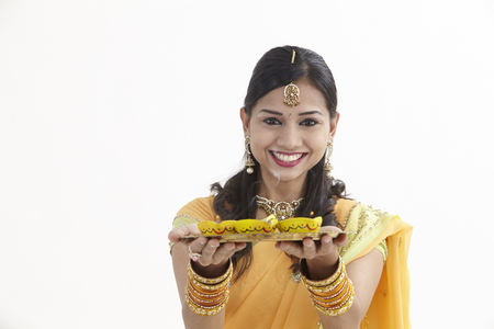 Indian woman in glamorous traditional clothing holding a tray of diyas Stock Photo