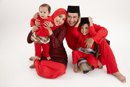 malay family sittng on the white background
