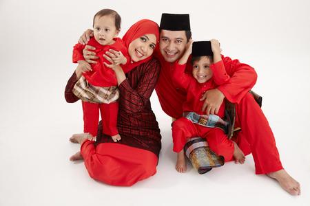 一个马来家庭坐在白色的背景上
