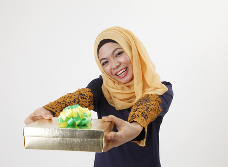 malay woman with tudung giving a present away