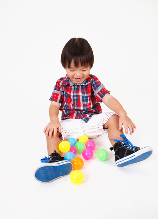 chinese boy sitting down playing with toys Фото со стока