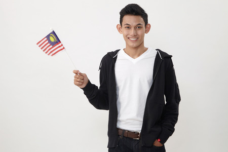 malay teenage holding a small malaysiasia flag 写真素材