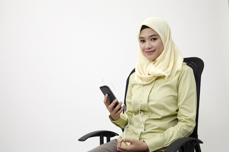 malay woman sittingon office chair  listen to music