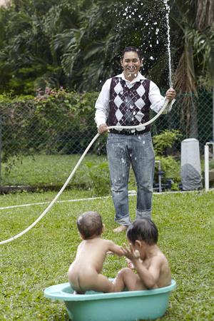 father splashing water to his boy