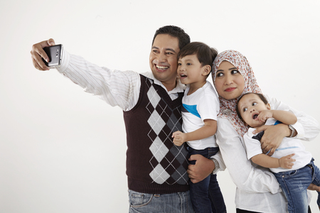 family of four looking taking selfie 版權商用圖片