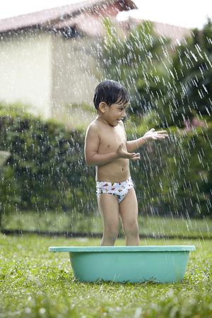 niño malayo disfrutando de tomar un baño al aire libre