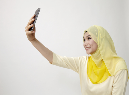 malay woman holding using smart phone self portrait 版權商用圖片