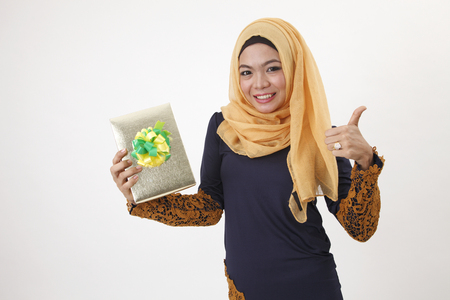 malay woman with tudung happy received a gift with thumb up