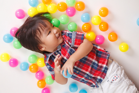 top view of chinese boy playing with colorful balls