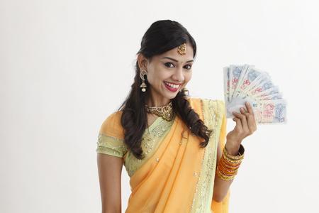 Mujer inadin en sari sosteniendo billetes en efectivo de Singapur