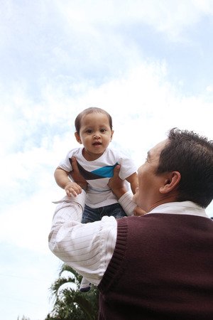 father playing with his baby in front of house Stock Photo