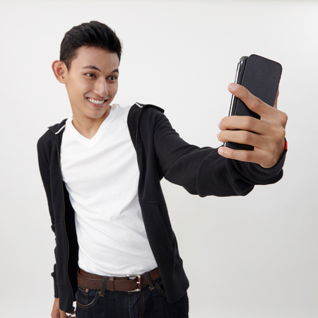 malay teenage doing selfing with his smart phone 版權商用圖片