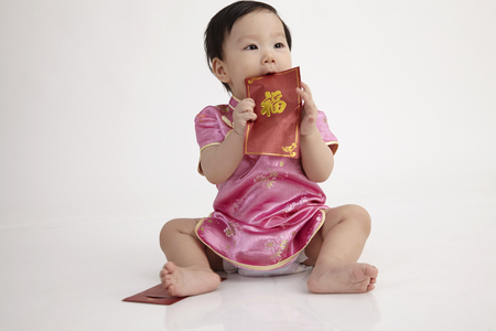 chinese baby wearing cheomgsam sitting in the studio playing with red envelope