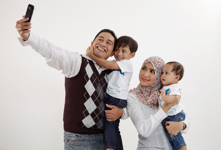 family of four looking taking selfie Stock Photo