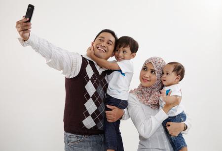 family of four looking taking selfie Standard-Bild